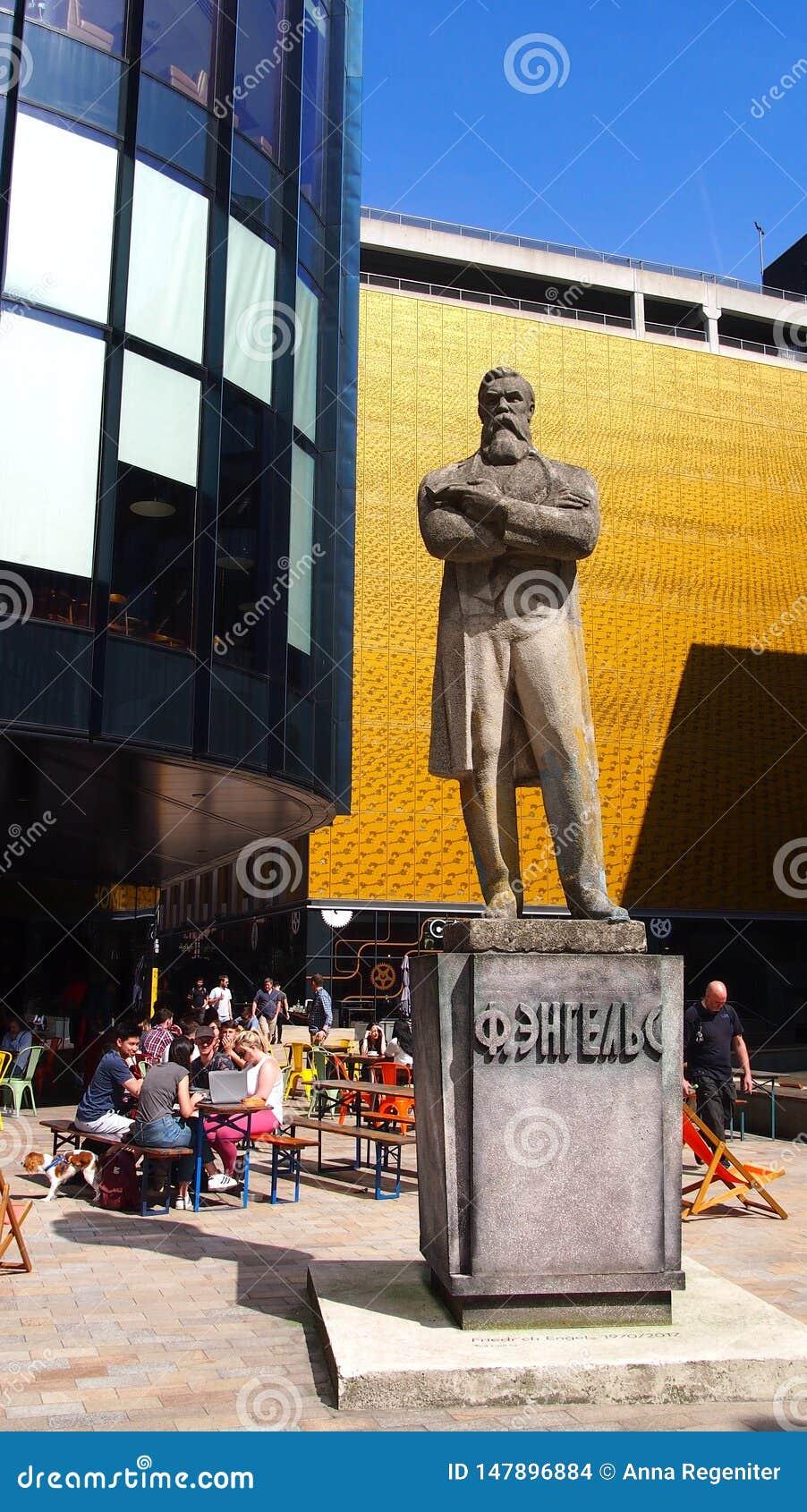 Staty av Friedrich Engels utanför den hem- kulturella mitten i Manchester, England