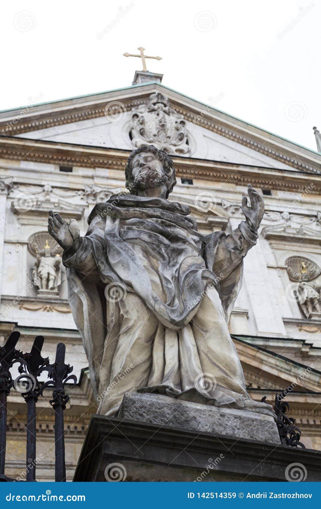 Staty av helgonet på bakgrunden av en medeltida kyrka med ett kors