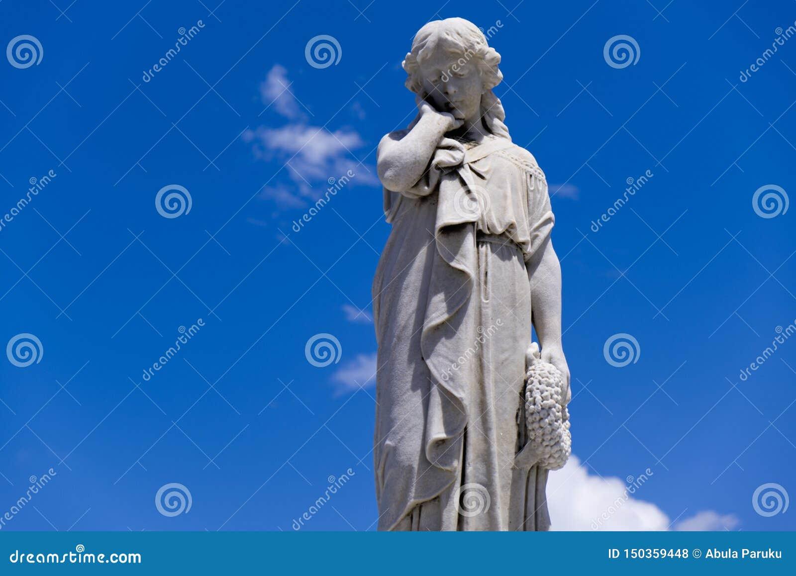 Staty för ung kvinna med handen på kind