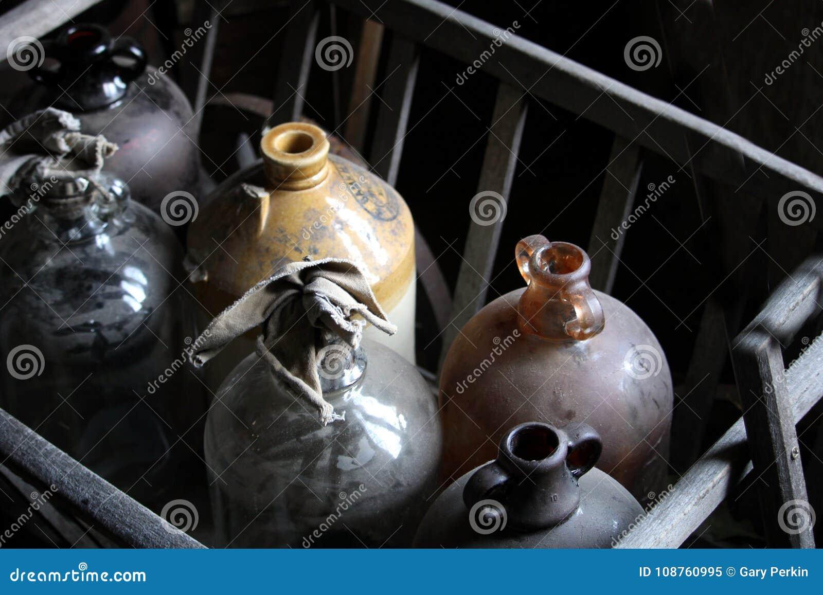 Staubige, rustikale alte Glaskorbflaschen oder Weinflaschen in einem hölzernen Ra