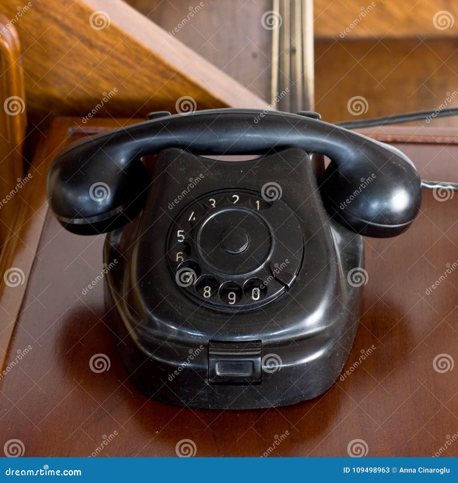 Staubiges schwarzes Telefon der alten Scheibenweinlese auf dem Schreibtisch