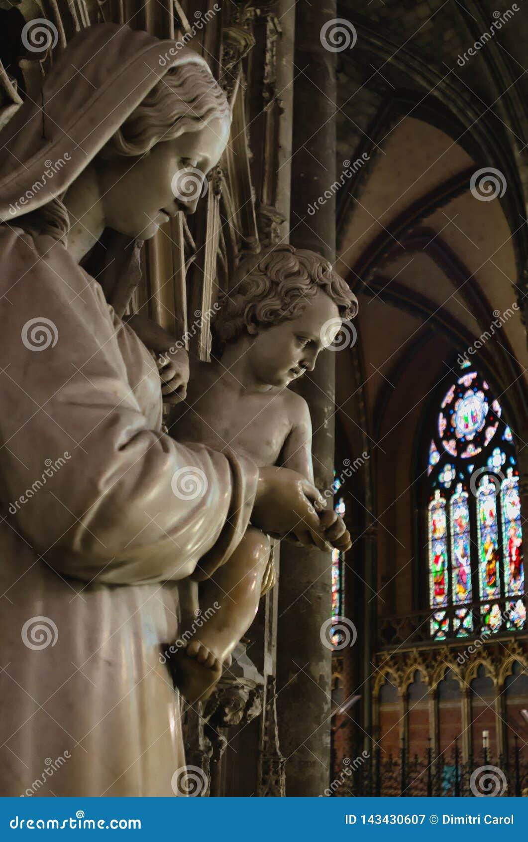 Staue da Mary santamente que guarda o bebê Jesus Christ dentro da catedral gótico de Saint-andré