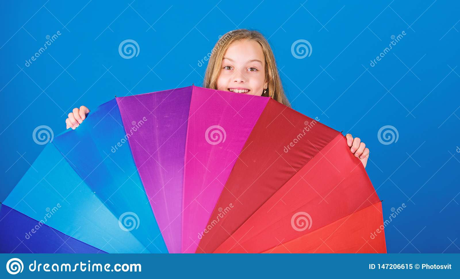 Stay positive though rainy day. Brighten up life. Kid peek out colorful rainbow umbrella. Color your life. Girl cheerful