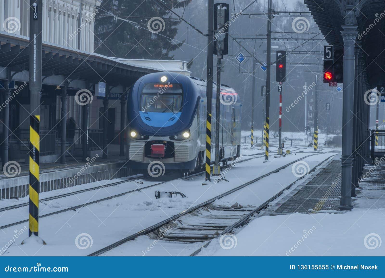 Stazione Marianske Lazne con i treni nel giorno di inverno scuro della neve