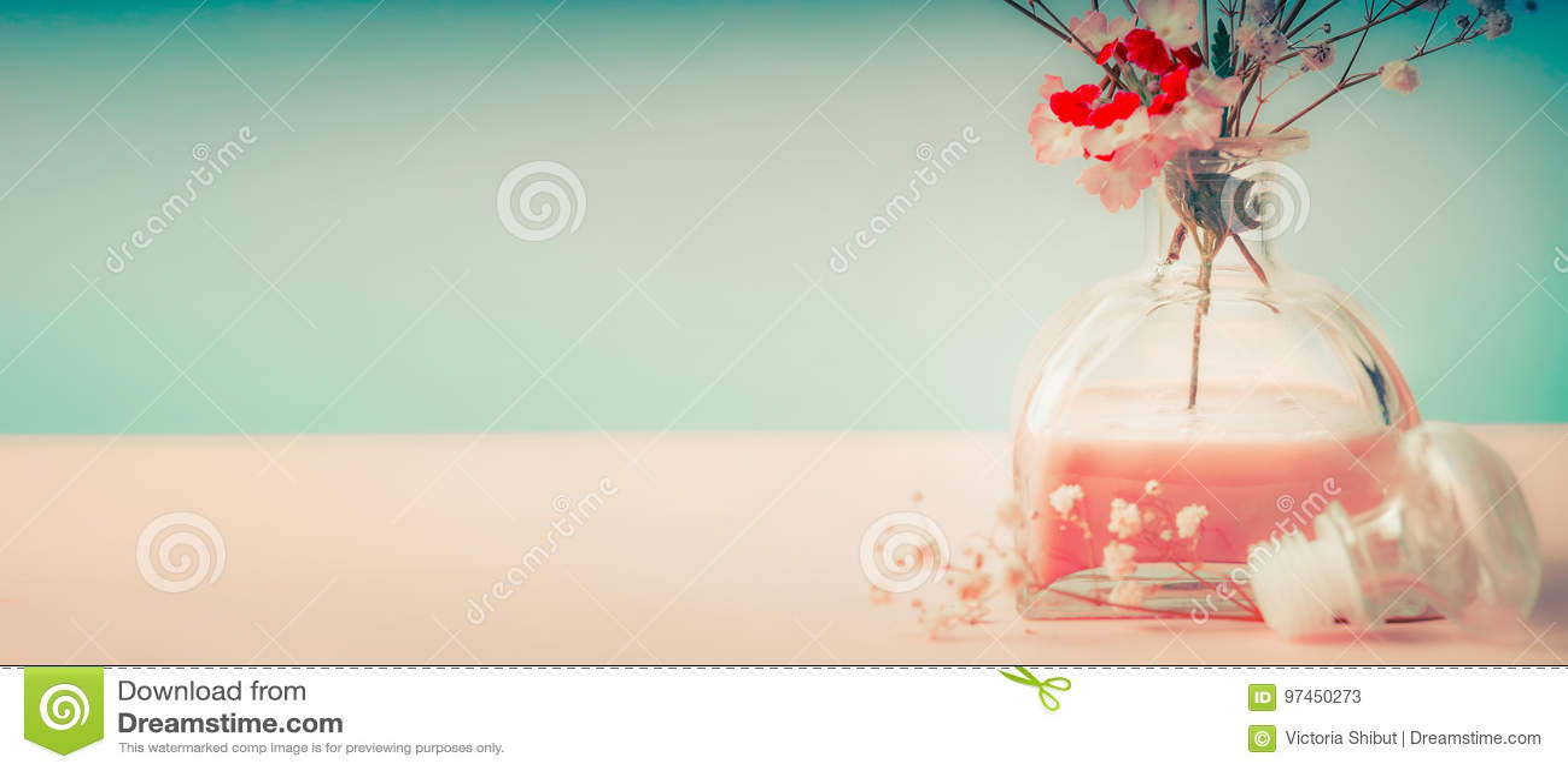 Stazione termale o fondo di benessere con la bottiglia ed i fiori di fragranza della stanza su fondo pastello, vista frontale