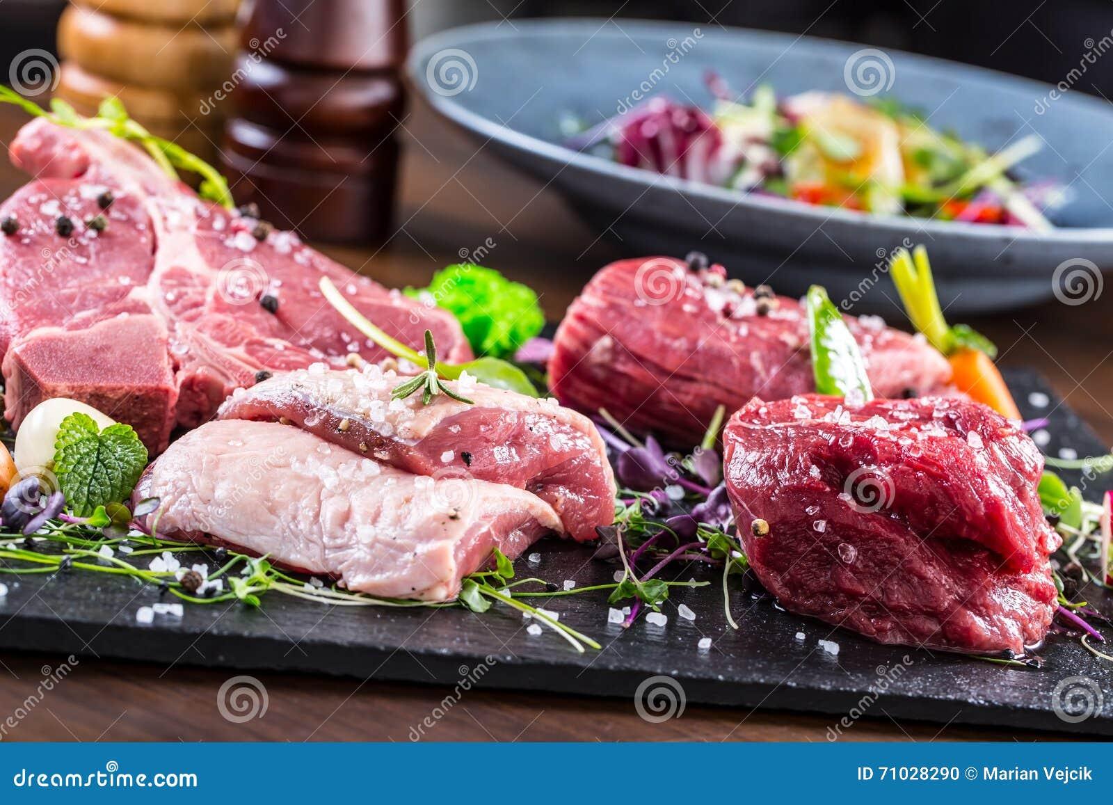 Steak.Beef steak.Meat.Portioned meat.Raw fresh meat.Sirloin steak.T-Bone steak. Flank steak. Duck breast. Vegetable decoration.