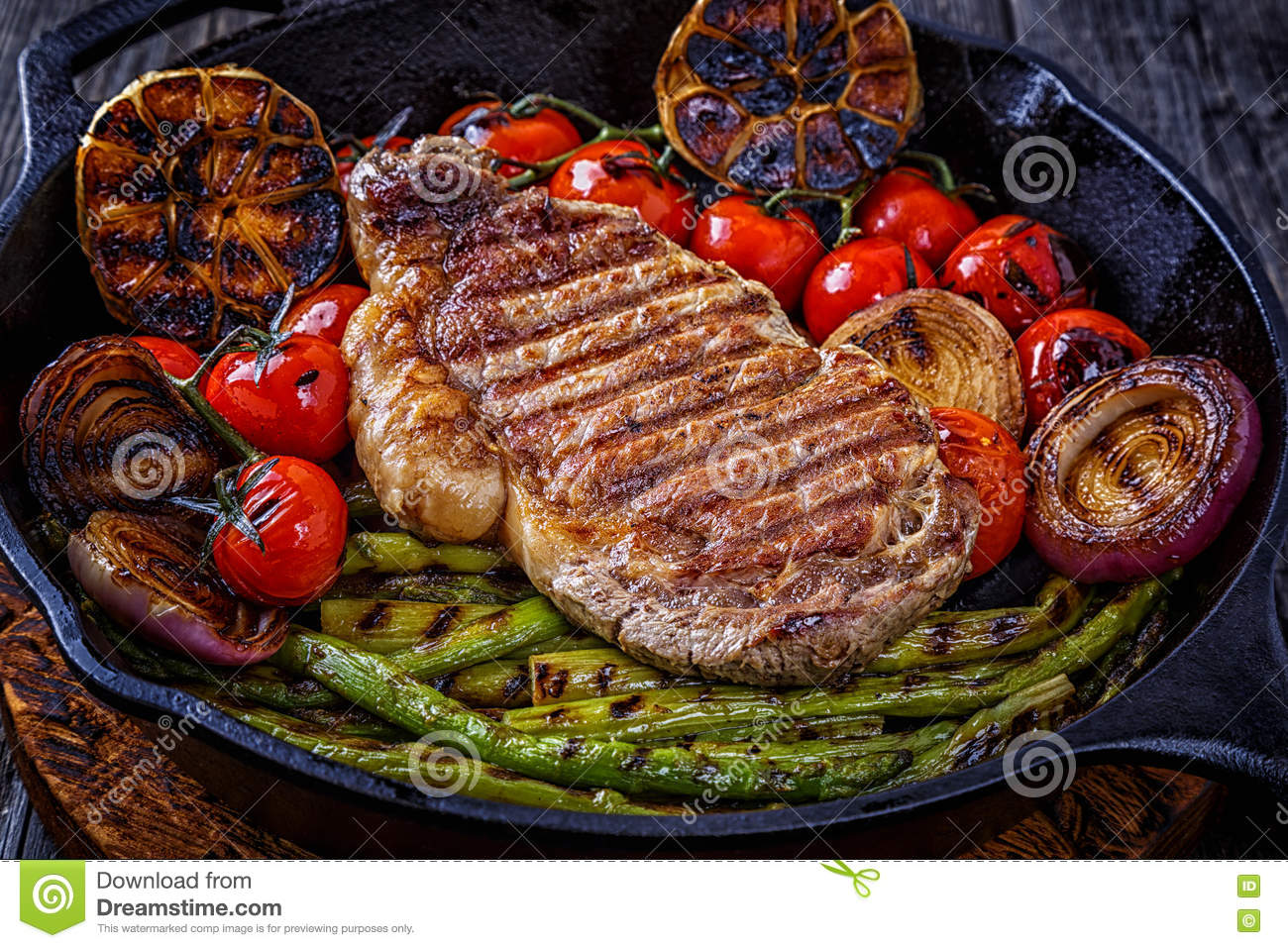 Steak with grilled vegetables in a frying pan.
