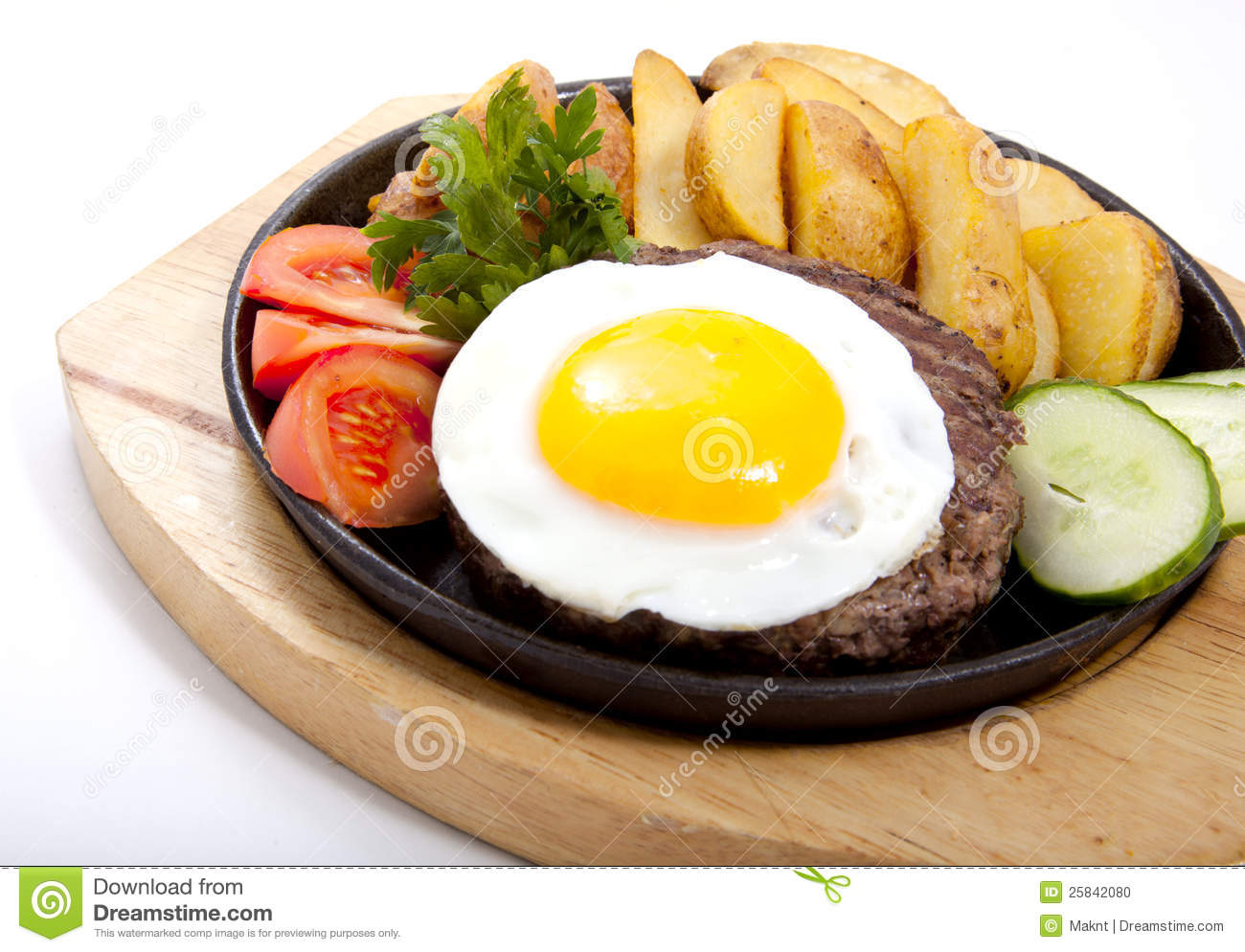 Photo of steak with potatoes and egg in a frying pan.