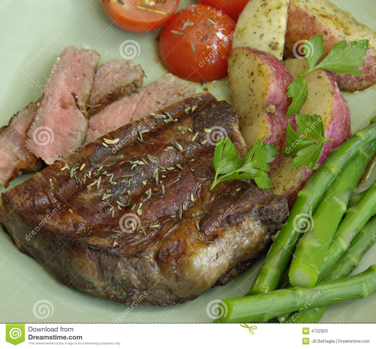 Grilled steak with roasted potatoes, tomatoes, and asparagus.