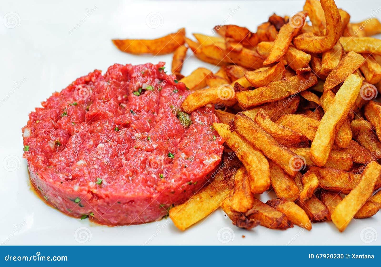 Novogodišnja gozba Steak-tartare-served-french-fries-potato-chips-raw-minced-beef-meat-white-67920230