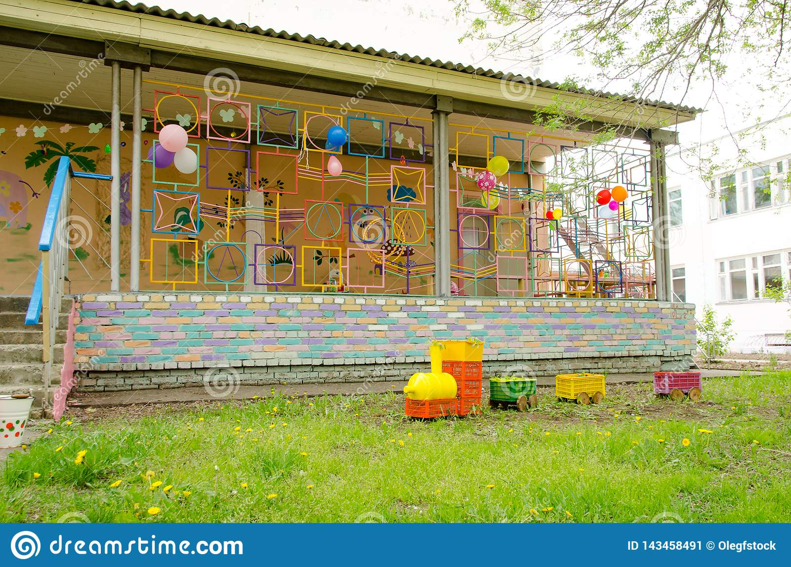 Steam locomotive made of plastic boxes and bottles on lawn next to terrace on playground