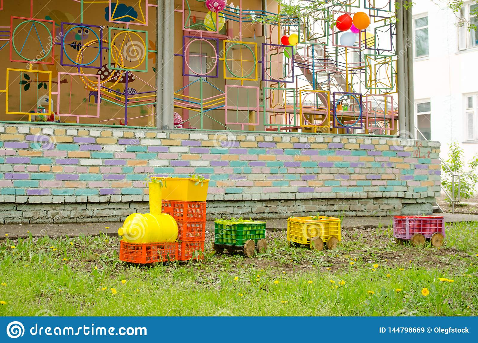 Steam locomotive made of plastic boxes and bottles on lawn on playground
