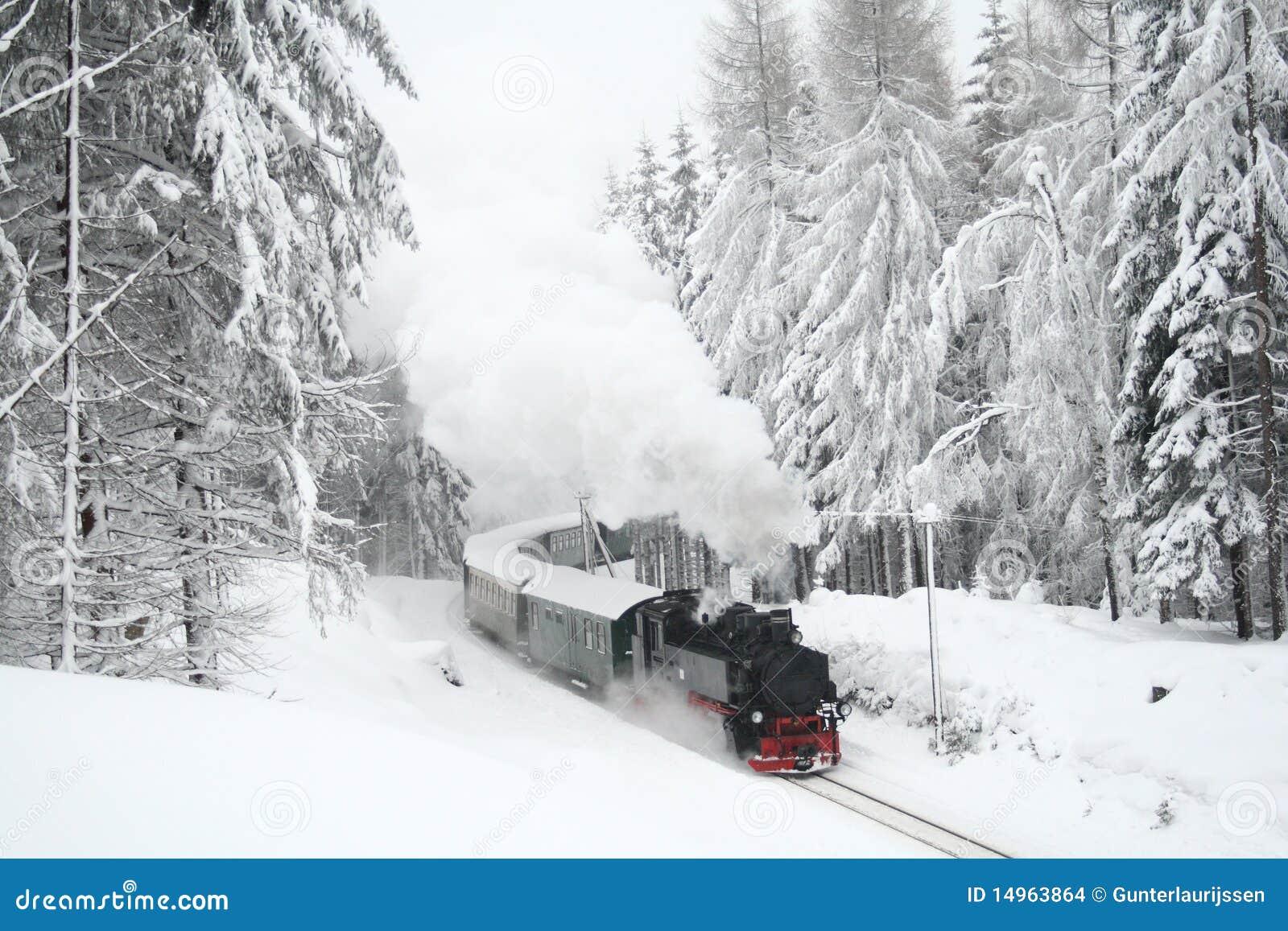 Steam Train Driving Through Snowy Woods Stock Photo