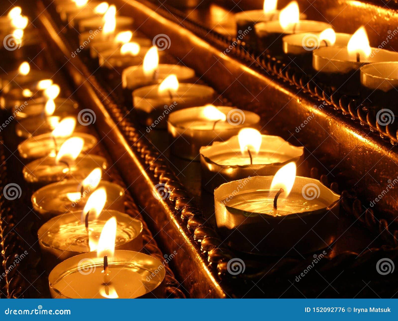 Stearinljus bränner på ljusstaken i kyrkan Kyrkliga redskap N?rbild