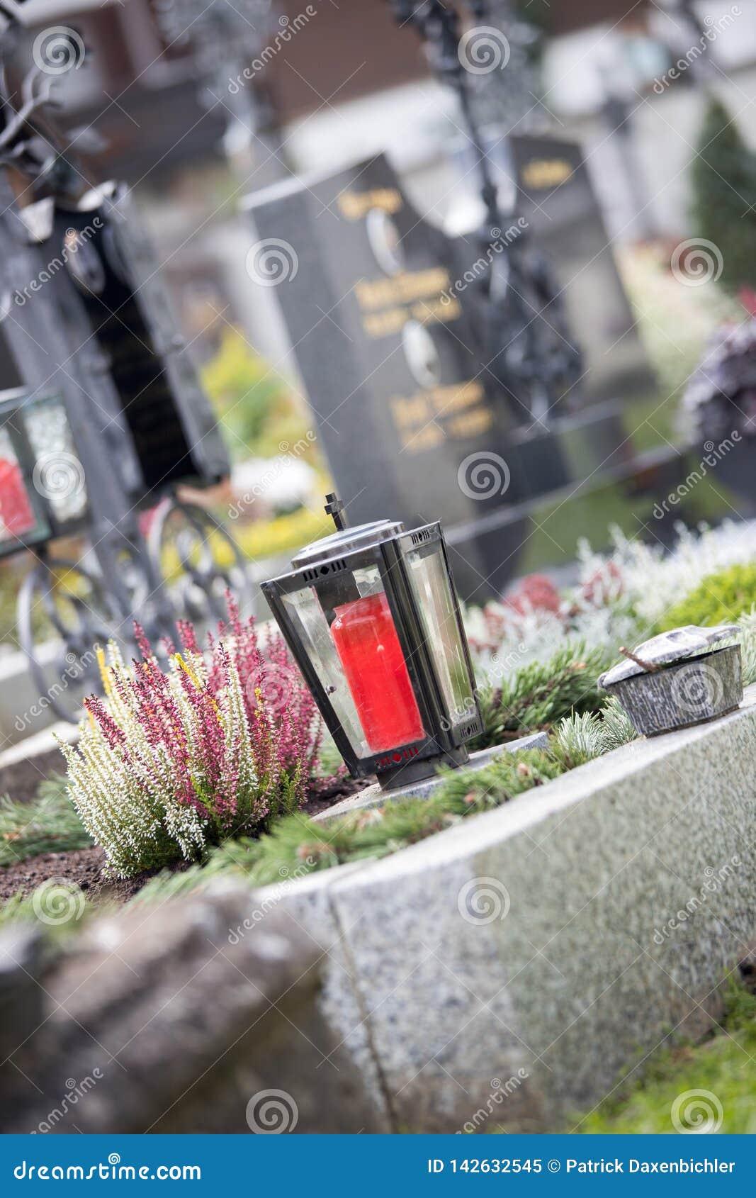 Stearinljus/lykta på kyrkogården, begravning, sorg