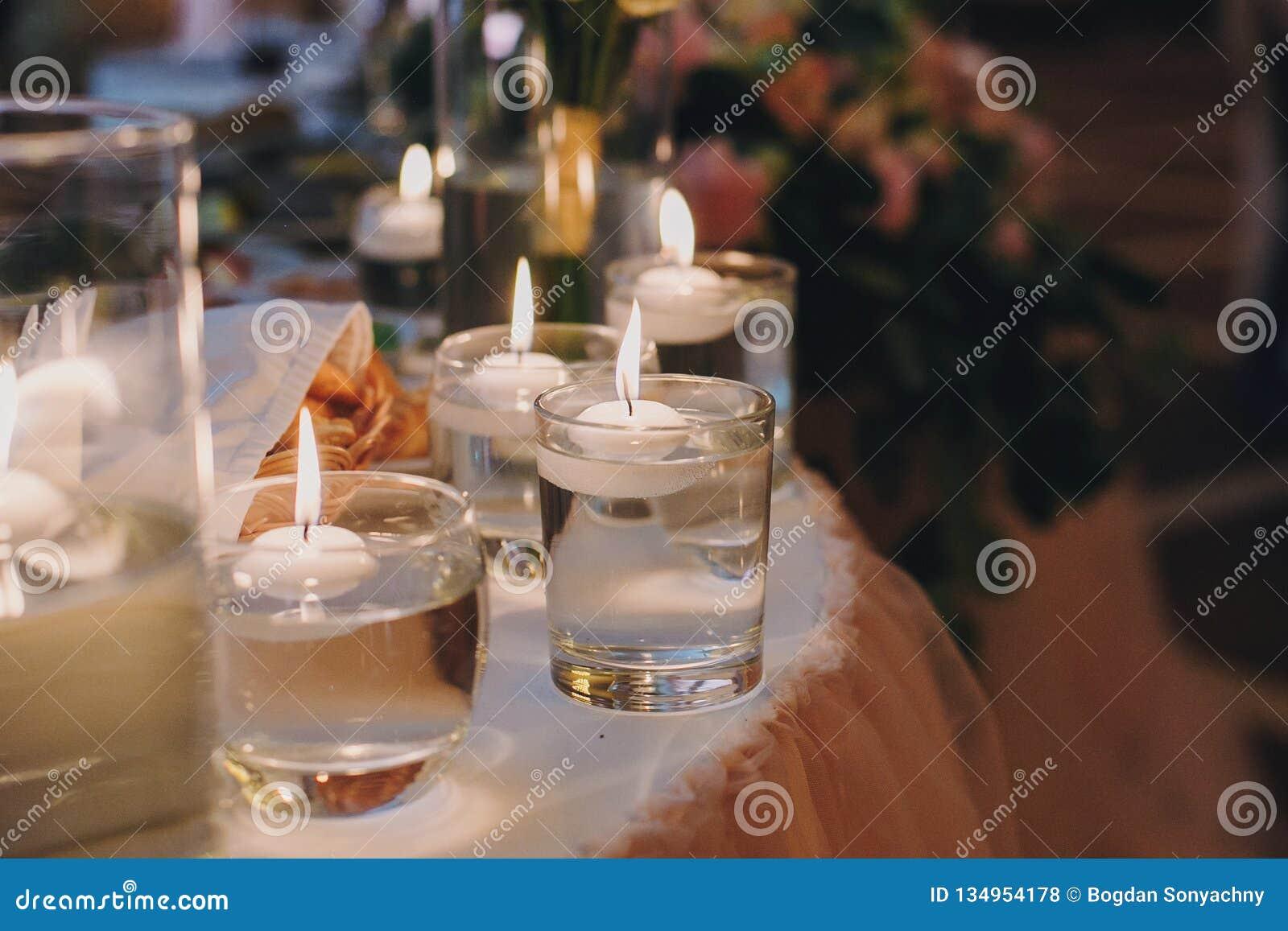 Stearinljus med ljus i exponeringsglas med vatten, stilfull gifta sig dekor för aftonceremoni eller på mottagandet i restaurang s