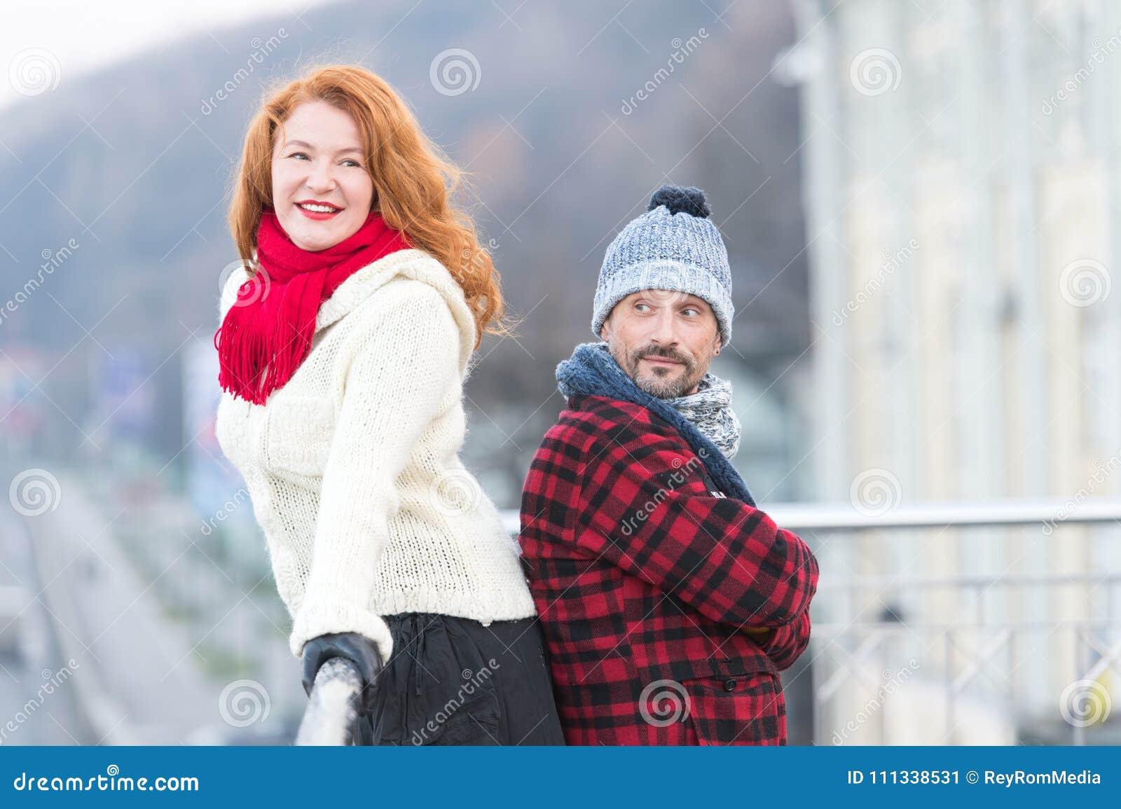 Stedelijk paar op de brug Gelukkig paar dat zich rijtjes bevindt De man en de vrouw kijken op één manier Glimlachende rode haarda