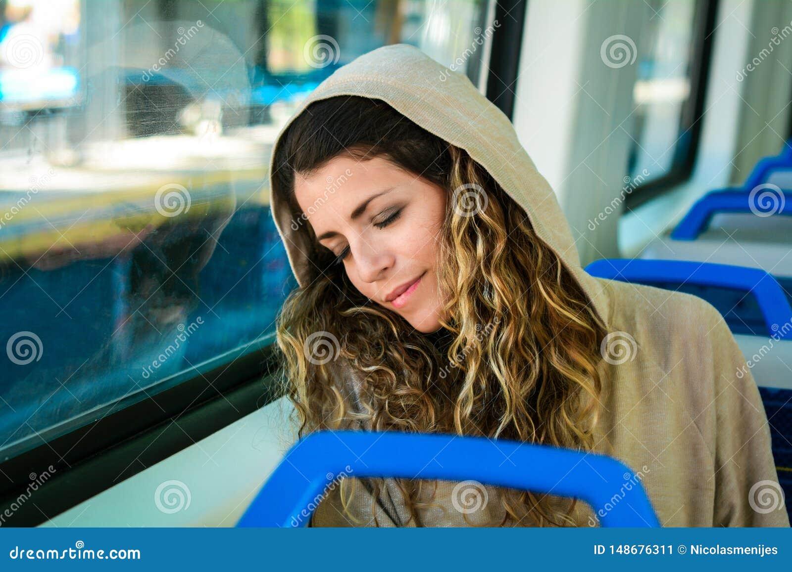 Stedelijke vrouwenslaap in een treinreis naast het venster