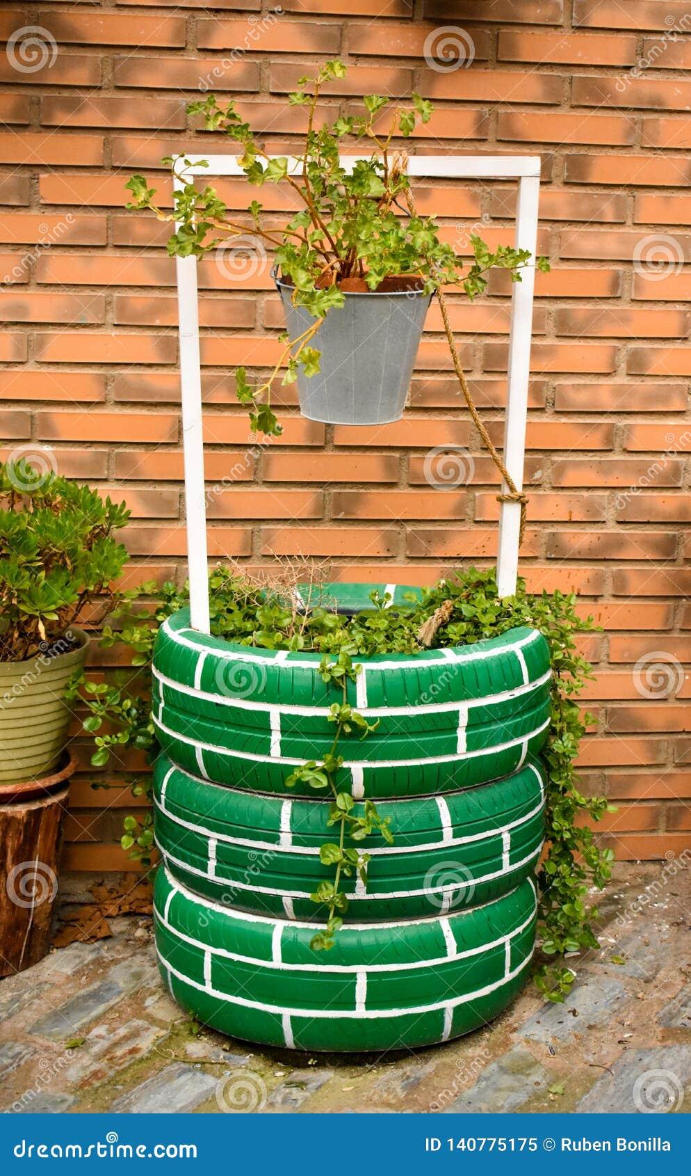 Stedelijke waterput die een stedelijke tuin met geschilderde banden verfraaien, een grijze emmer met installaties op een baksteen