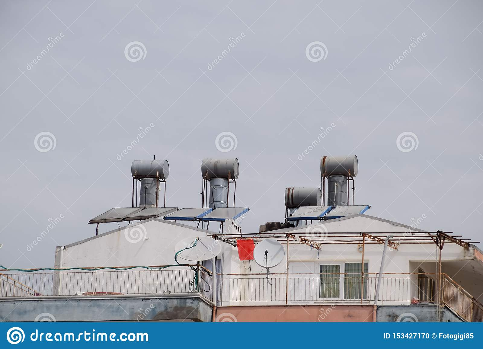Steel barrels of boilers with water on the roof of a building to heat water