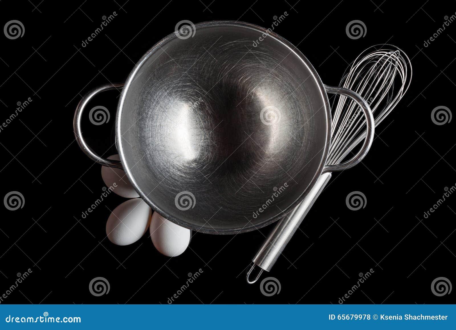 Steel bowl whisker eggs from above on black