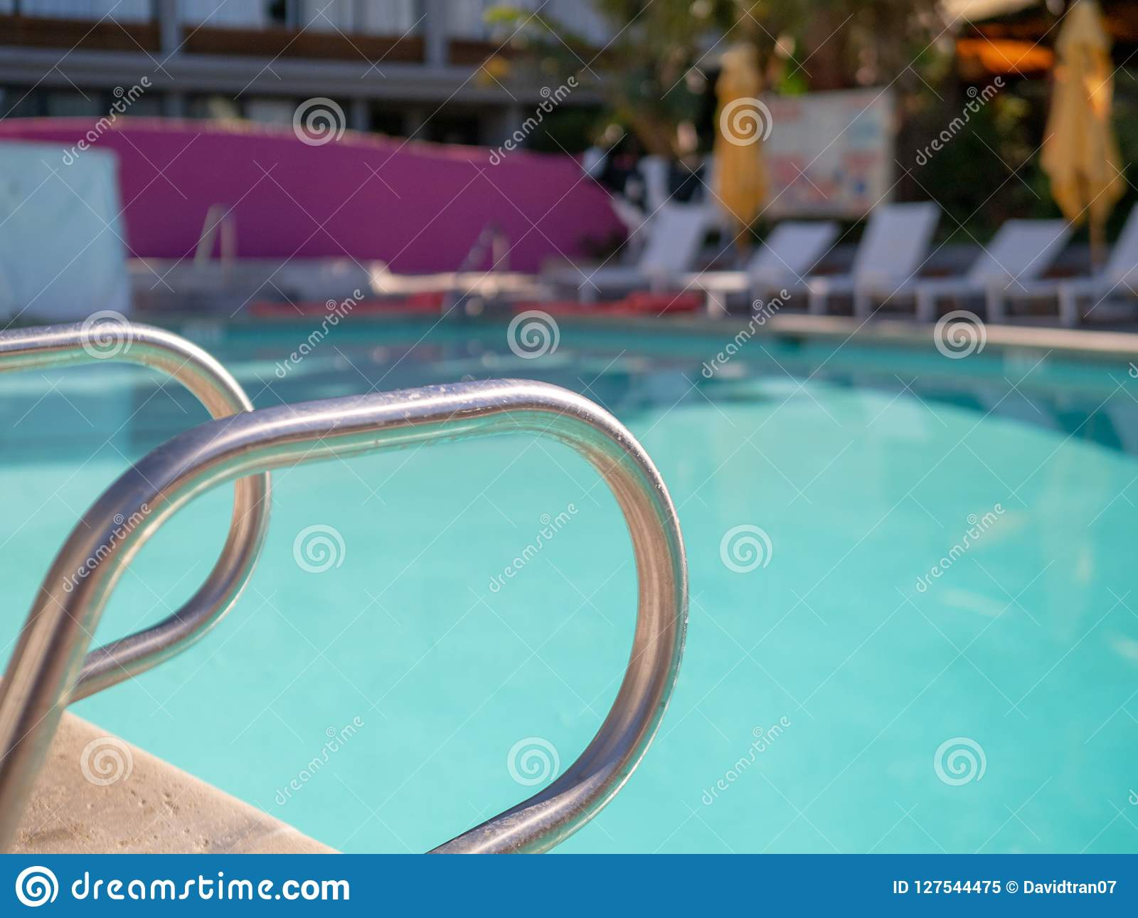 Steel handrail entrance assist to outdoor pool on sunny day