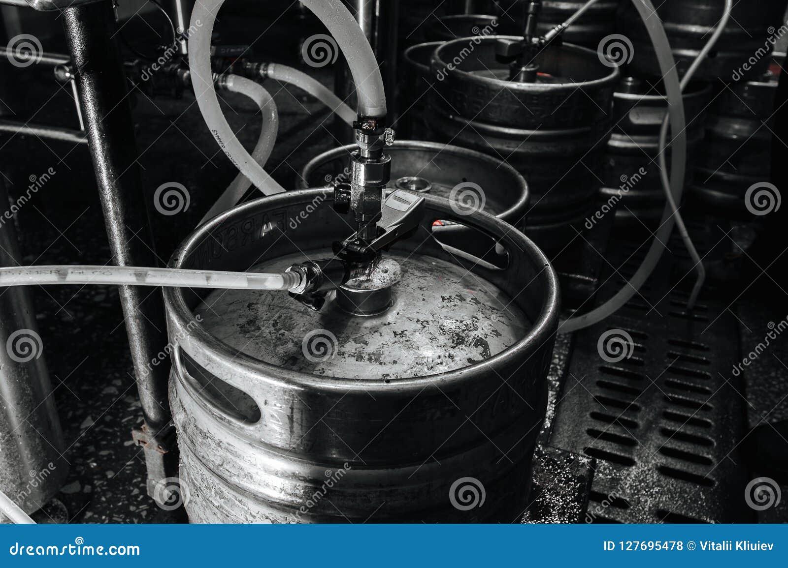 Steel industrial stack of beer kegs against.