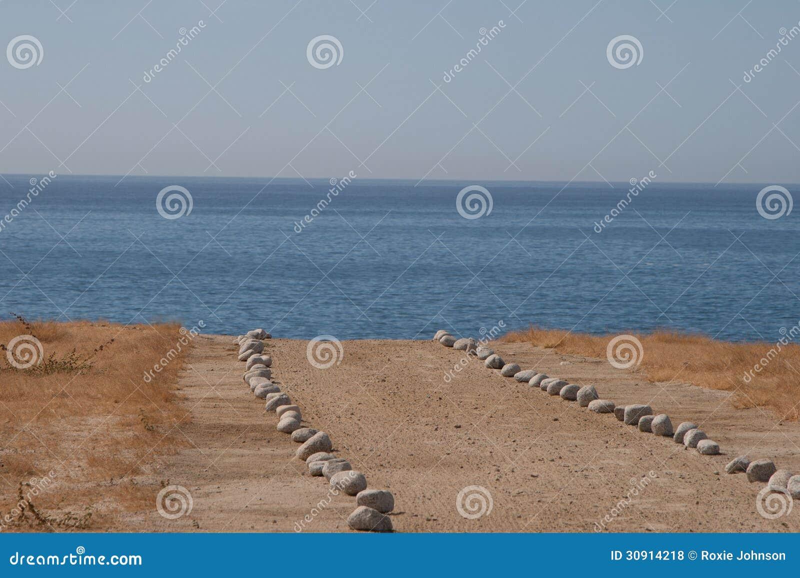 Steen gevoerde weg op strand stock foto afbeelding bestaande uit