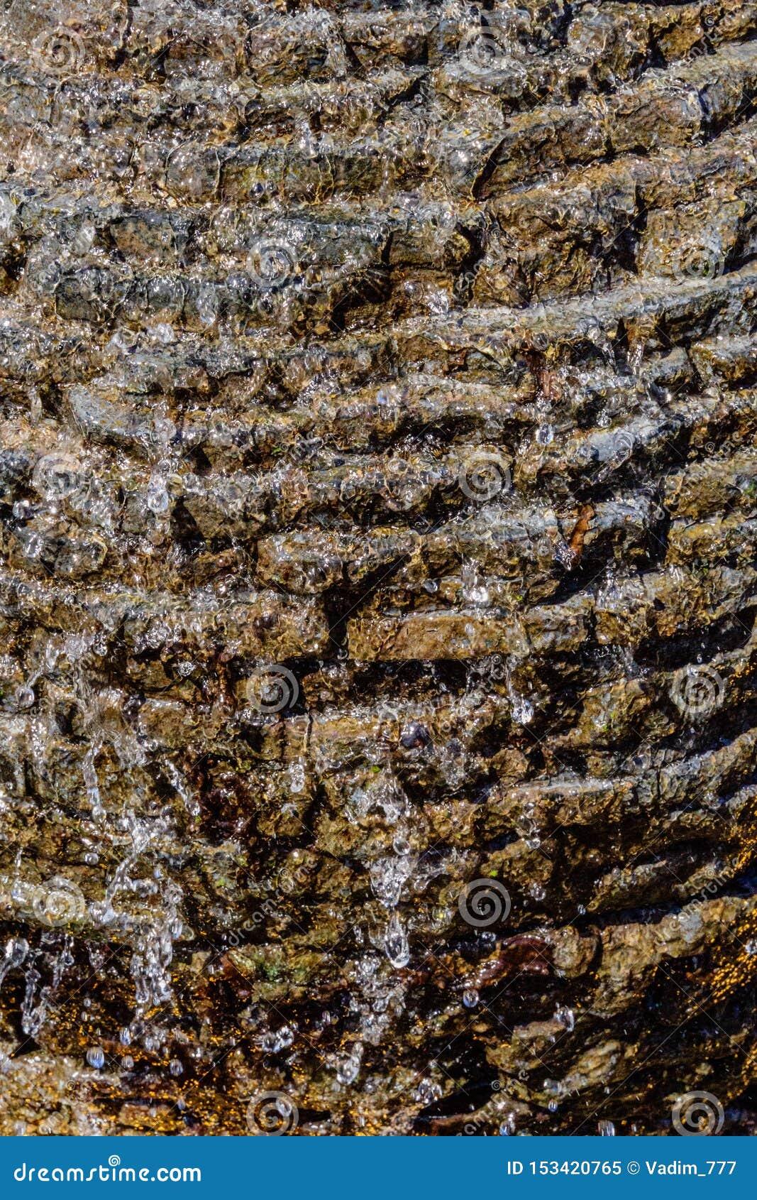 Steenmetselwerk met lopend water die neer met van het achtergrond waterschuim textuur stromen