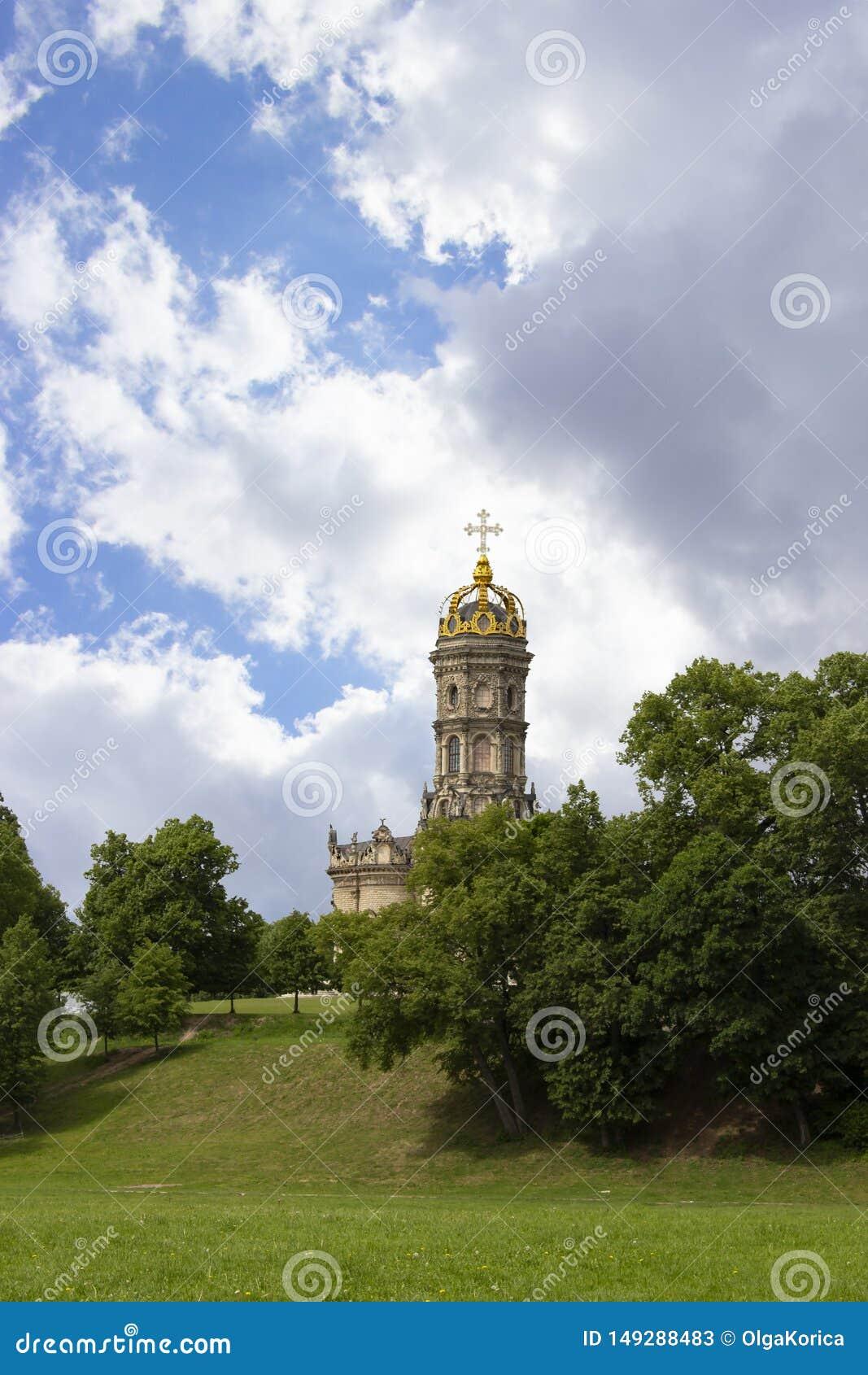 Steentempel met een hoge klokketoren, ??n gouden koepel en een gouden Christelijk kruis op bovenkant Mooie majestueuze orthodox