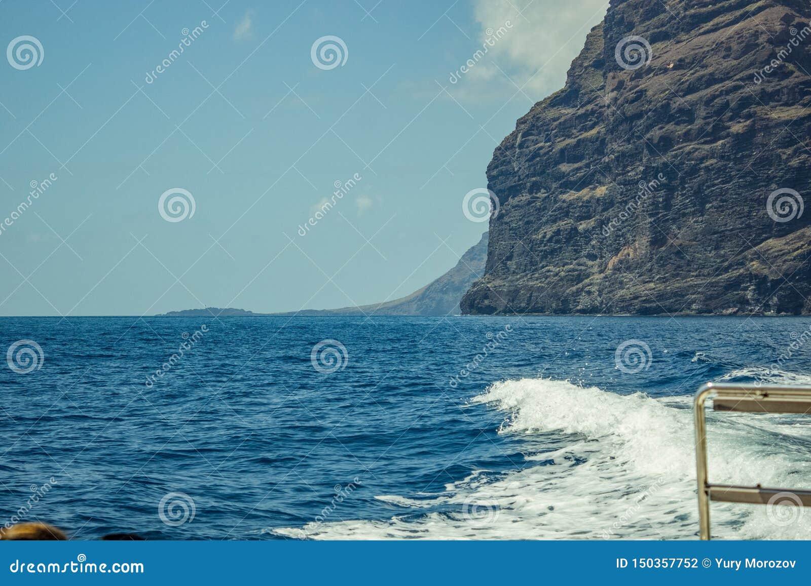 Steep high lava rock cliffs. Blue sea horizon, natural sky background