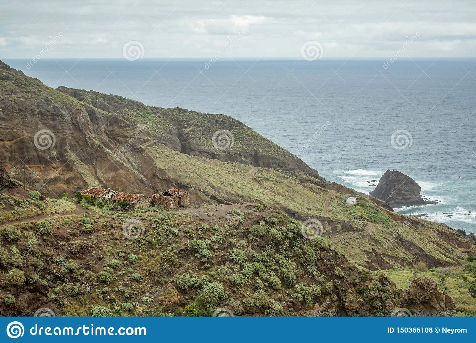 Steep high lava rock cliffs on on the east of Tenerife. Solitary rocks sticking out of the water. Old abandoned huts. Blue sea