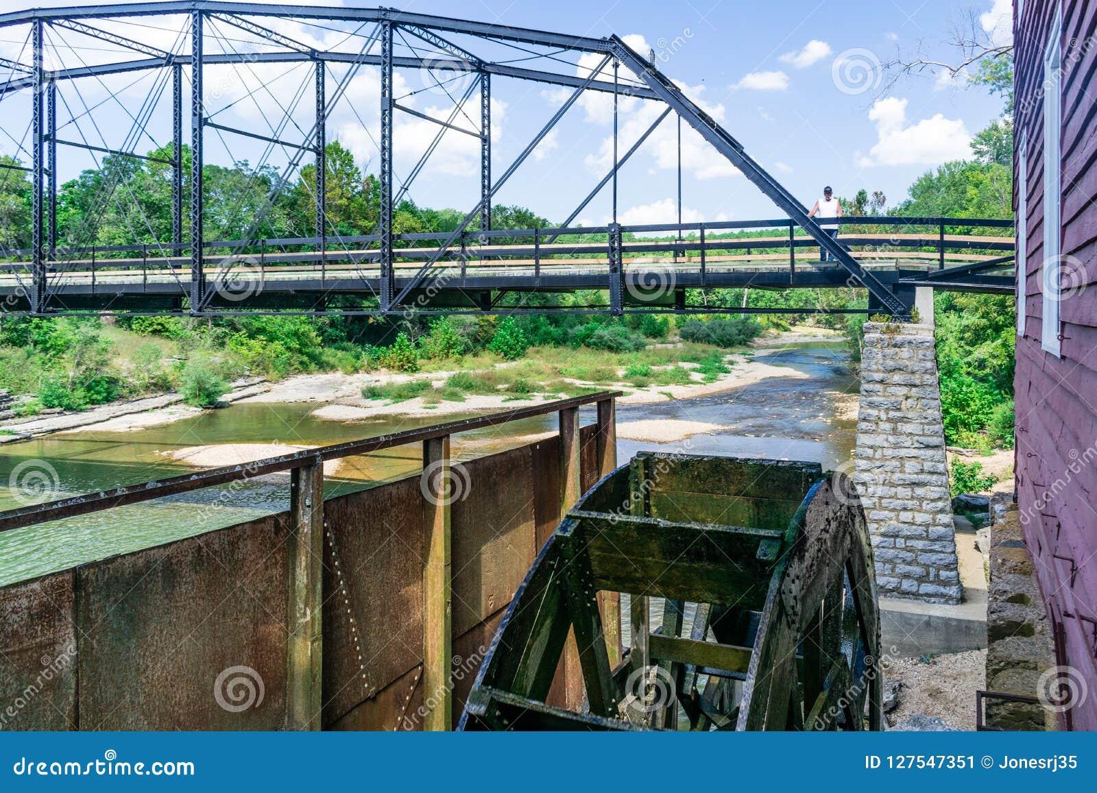 Stehend auf dem historischen Krieg Eagle Bridge in Rogers, kann Arkansas man das Arbeitswasserrad sehen, das durch den Krieg Eagl