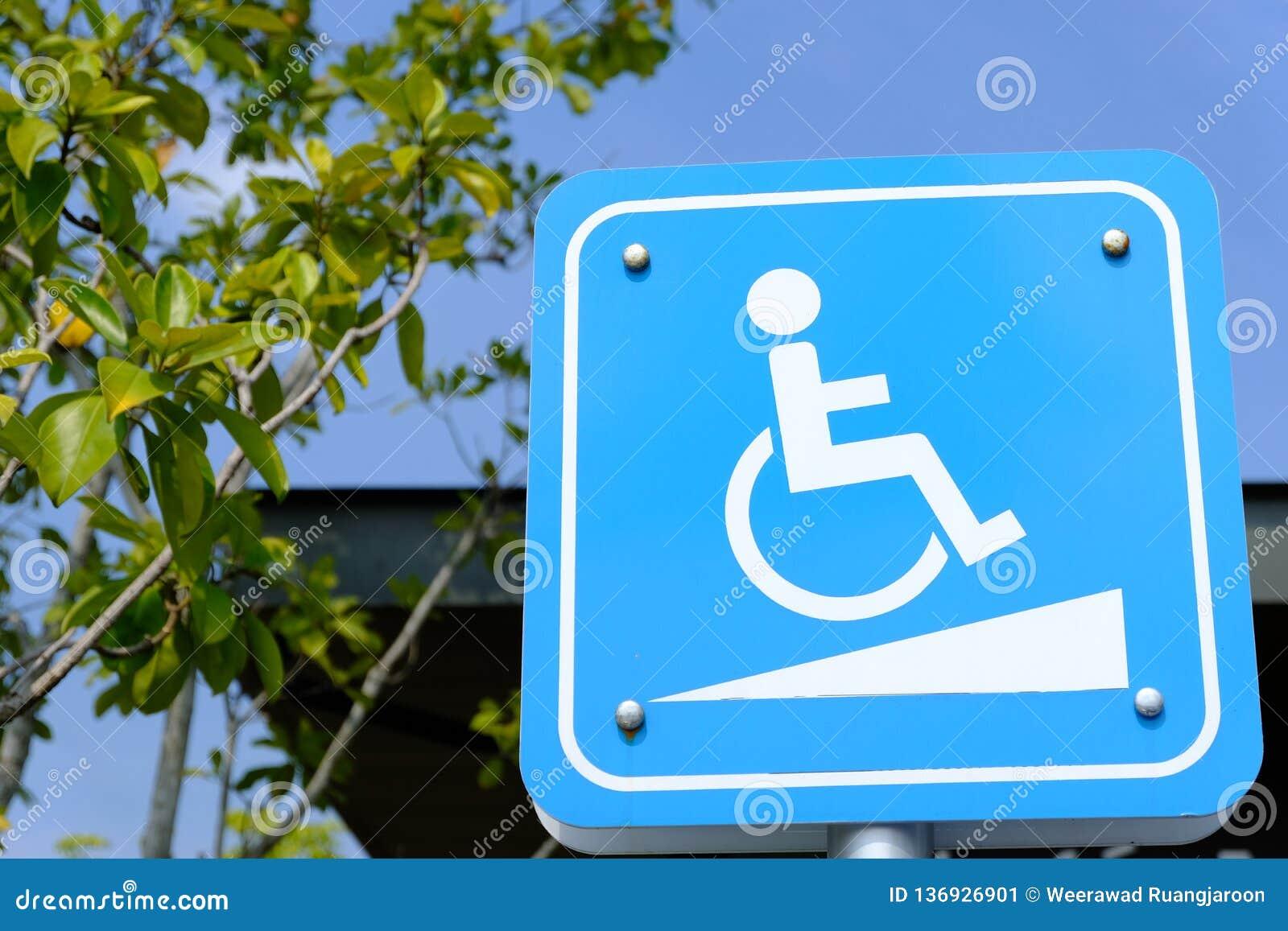 Steigungsweisenzeichen für Rollstuhlleute auf Hintergrund des blauen Himmels - behindertes Parken
