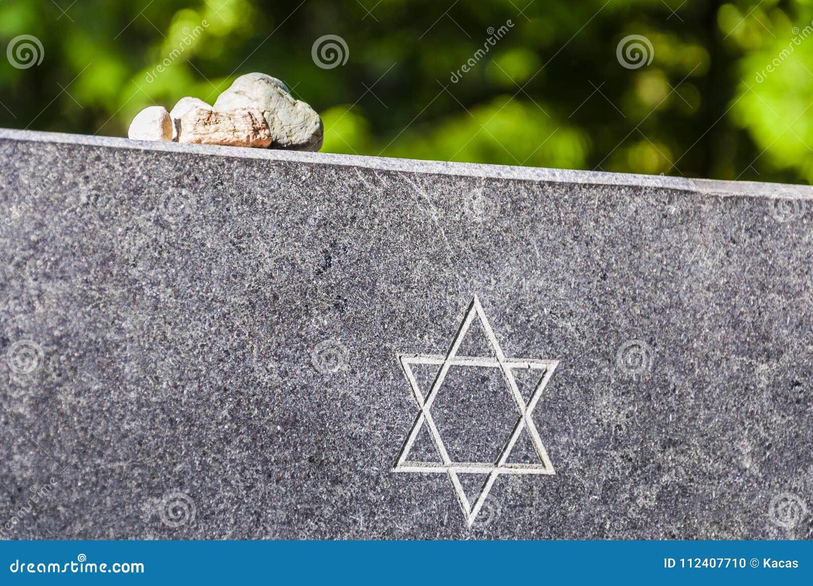 Steine auf jüdischer Erinnerungsgranitplatte mit Davidsstern