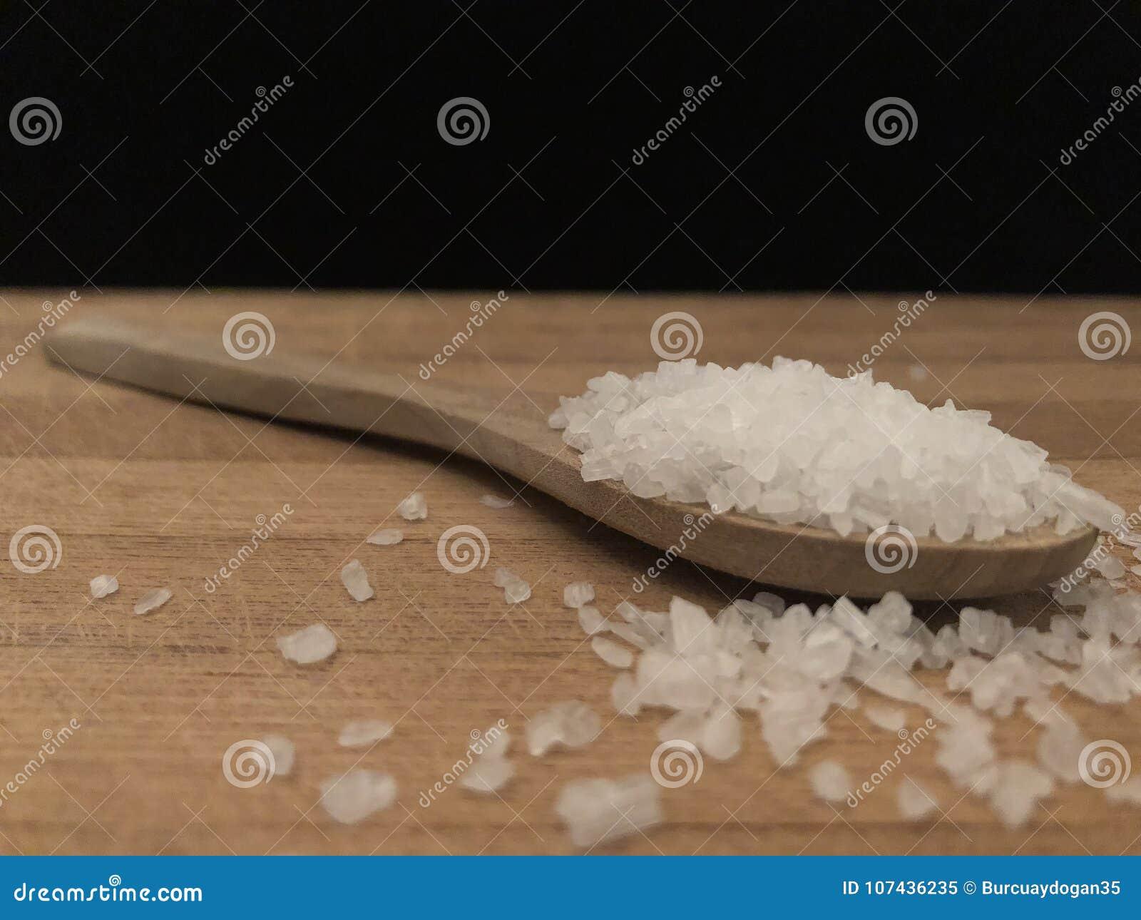 Steinsalz im hölzernen Löffel auf dem hölzernen Schneidebrett mit schwarzem Rückenbrett
