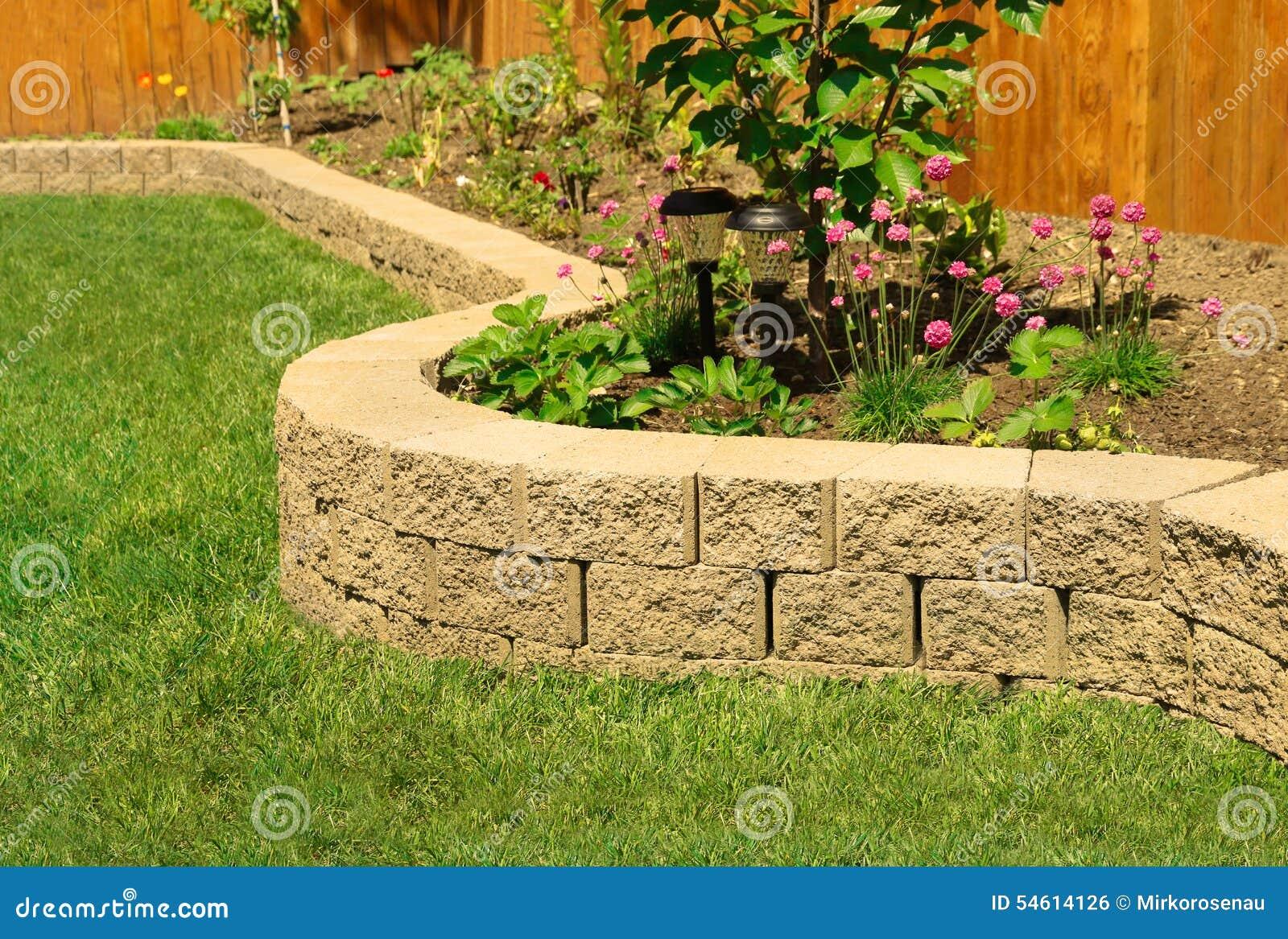 steinwand mit dem perfekten gras das im garten mit k nstlichem gras landschaftlich gestaltet. Black Bedroom Furniture Sets. Home Design Ideas