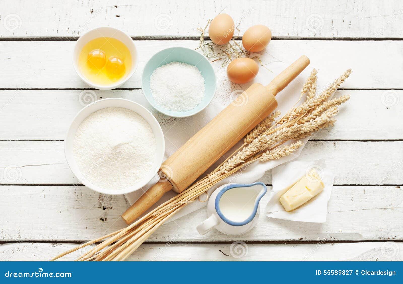 Stekhet kaka i lantligt kök - degreceptingredienser på den vita trätabellen