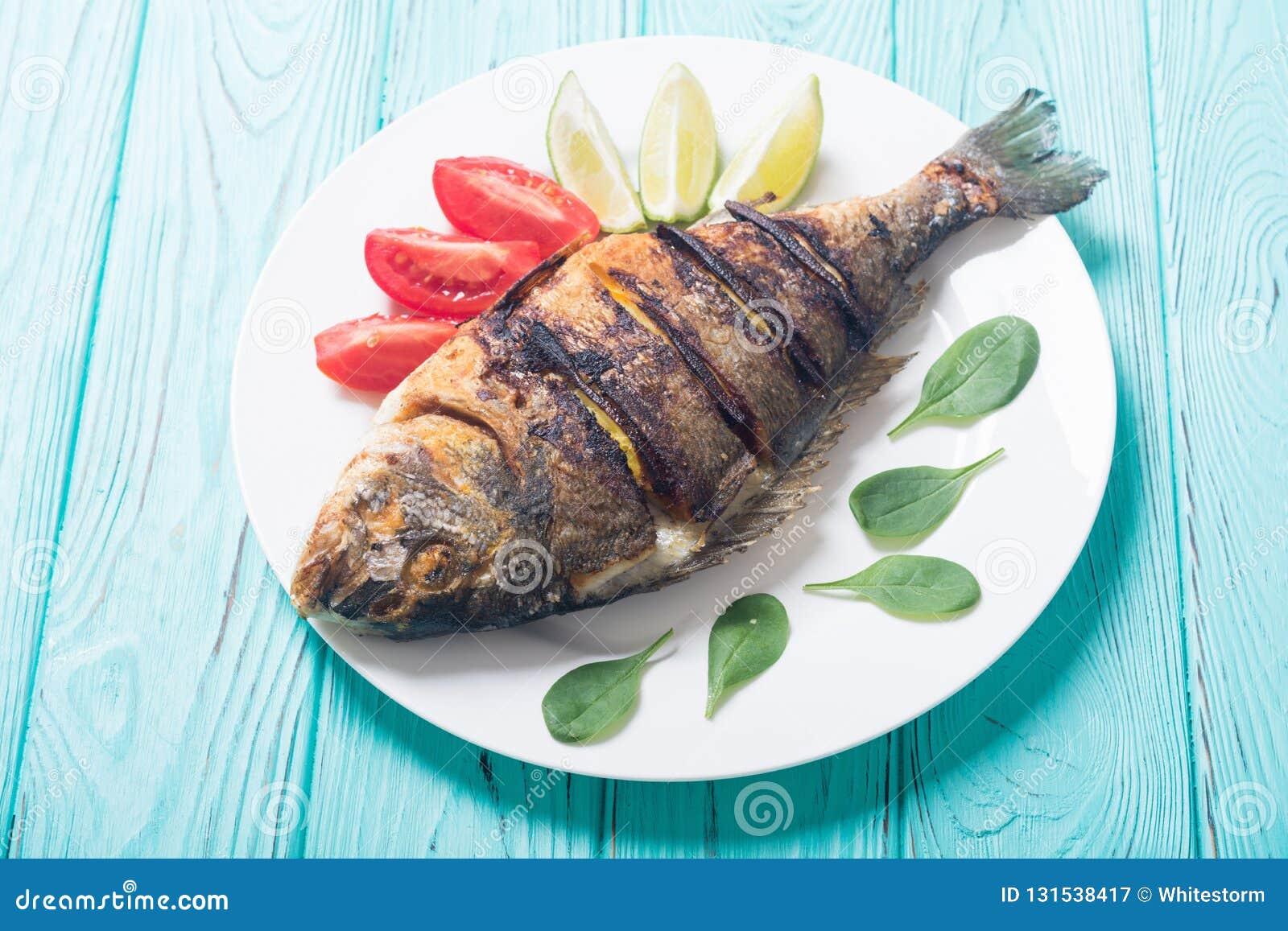 Stekt fiskdorado med limefrukt, tomater och spenat grillat hav för fiskmatparsley platta