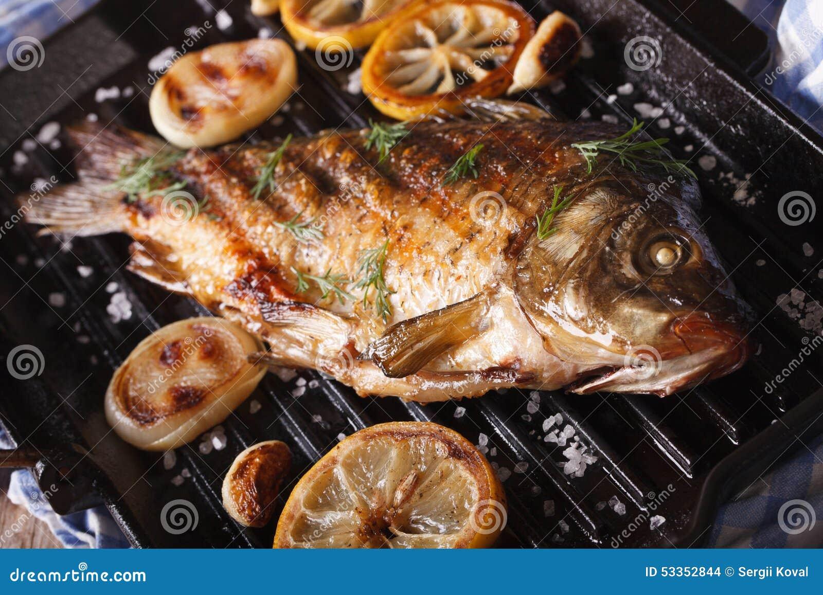Stekt fiskkarp med citronen och löken på gallerpannan