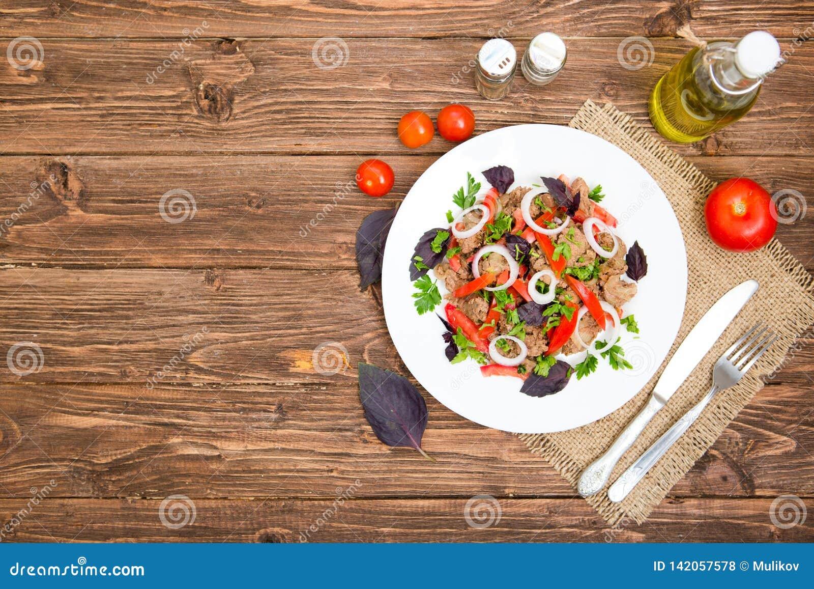 Stekt lever med löken och tomater på träbakgrund