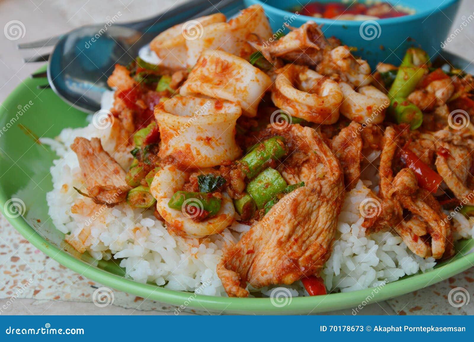 Stekt under omrörning currytioarmad bläckfisk och griskött på ris
