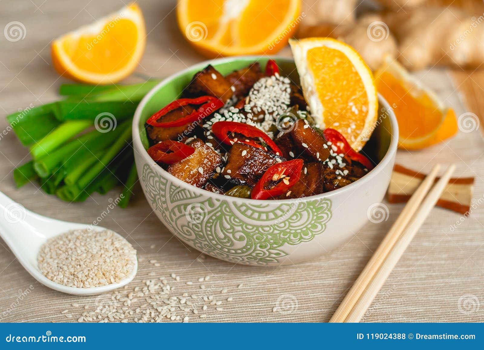 Stekt under omrörning orange ljust rödbrun tofu med sesamlök- och chilikryddor i en bunke med pinnar på en tabell