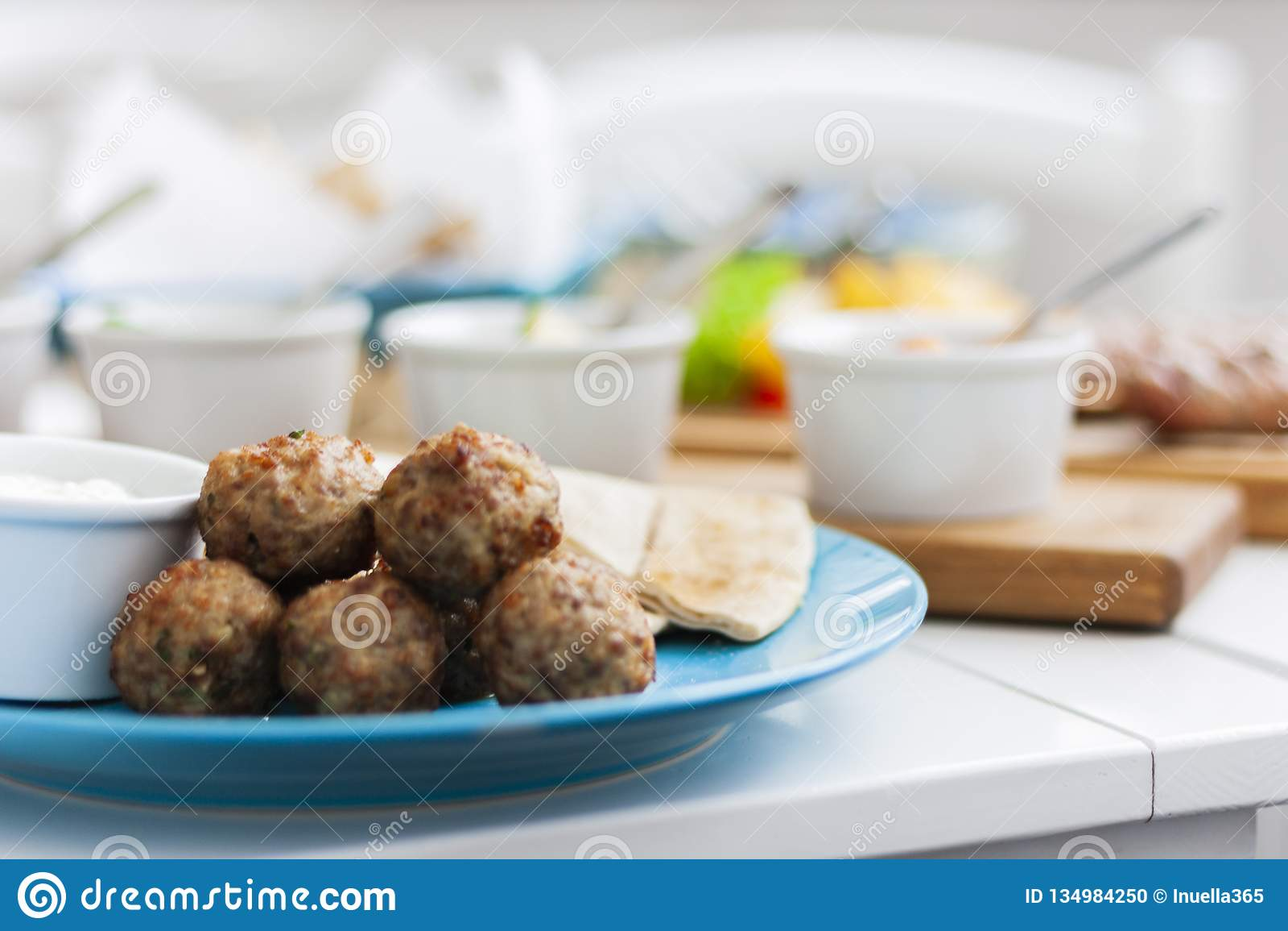 Stekte köttbollar med mintkaramellen och äpplet med vit sås och plana kakor - traditionell grekisk lunch på en blå platta i en re