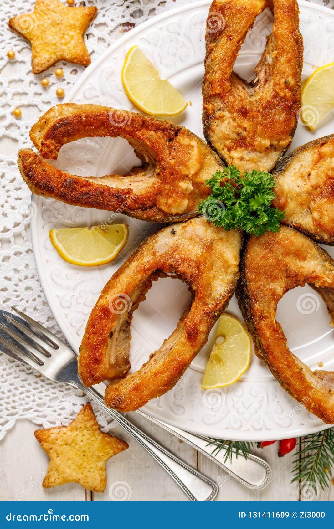 Stekte karpfiskskivor på en vit platta, bästa sikt Traditionell maträtt för julhelgdagsafton