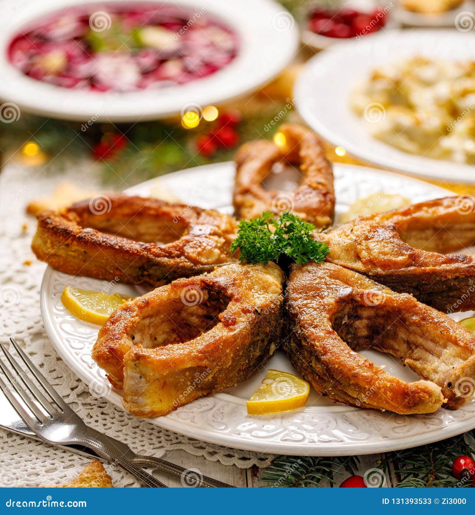 Stekte karpfiskskivor på en vit platta, slut upp Traditionell maträtt för julhelgdagsafton