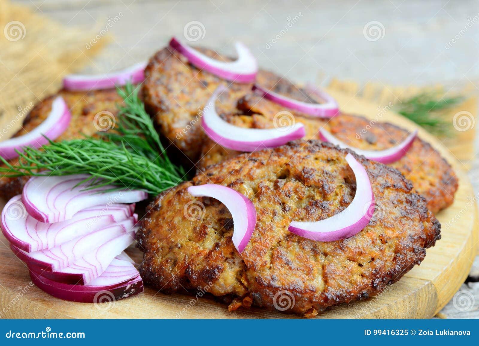 Stekte kotletter som göras från färs och grönsaker för feg lever Fastar enkla leverkotletter på en träskärbräda closeup