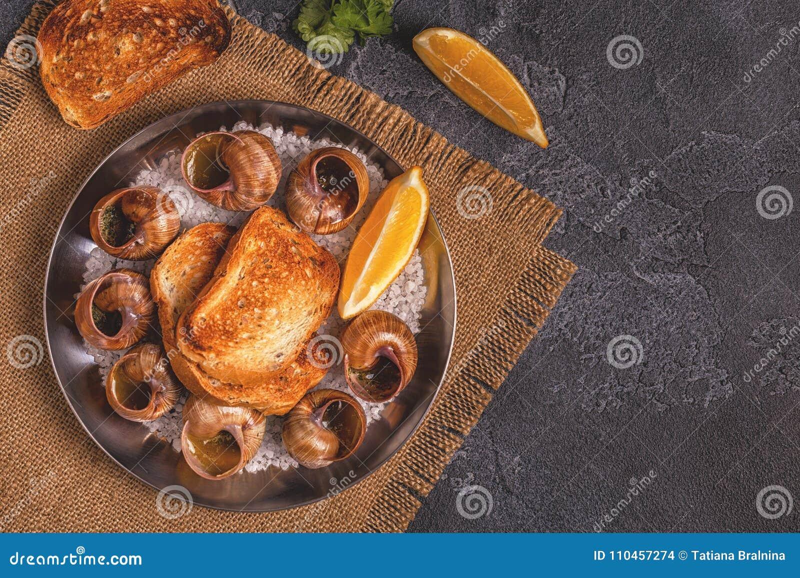 Stekte sniglar med citronen, bagetten och persilja