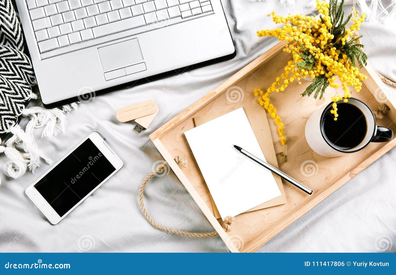 Stellen Sie Mit Blumen Und Einem Bett Des Laptops Morgens Mit Arbeit