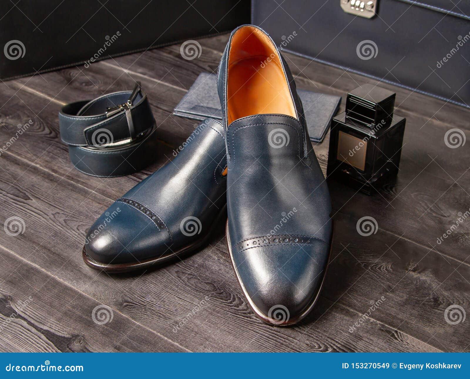 Stellen Sie von den blauen Schuhen der klassischen Männer, von der Geldbörse, vom Hosengurt und von einer Flasche Parfüm der Männ